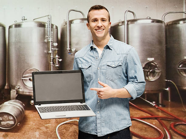 Smiling man pointing at laptop in brewery stock photo