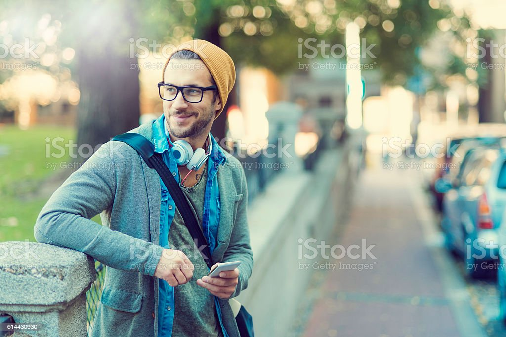 smiling man relaxing after work playing with his phone stock photo