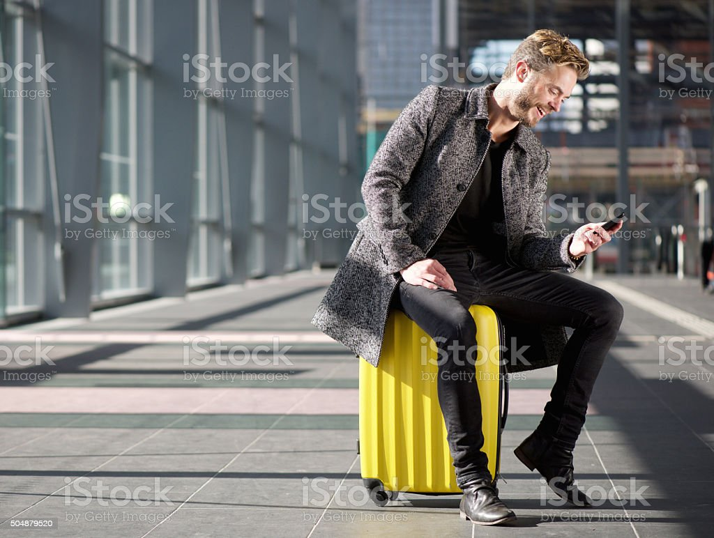 Smiling man resting at airport with mobile phone stock photo