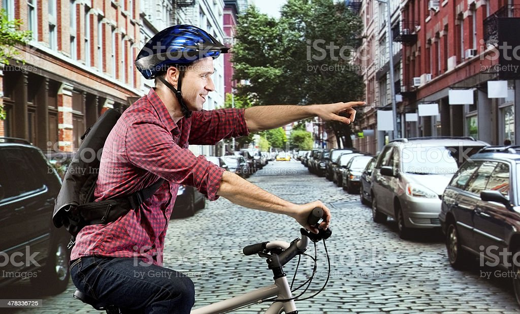 Smiling man riding bicycle on street and pointing royalty-free stock photo