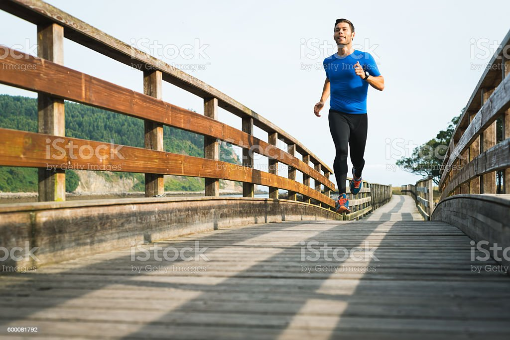 Smiling man running in park on wooden walkway working out – Foto