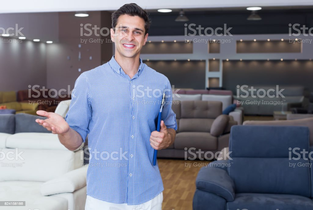 Smiling man seller showing prices in shop stock photo