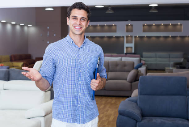Smiling man seller showing prices in shop Smiling man seller showing prices in home furnishings store salesman stock pictures, royalty-free photos & images