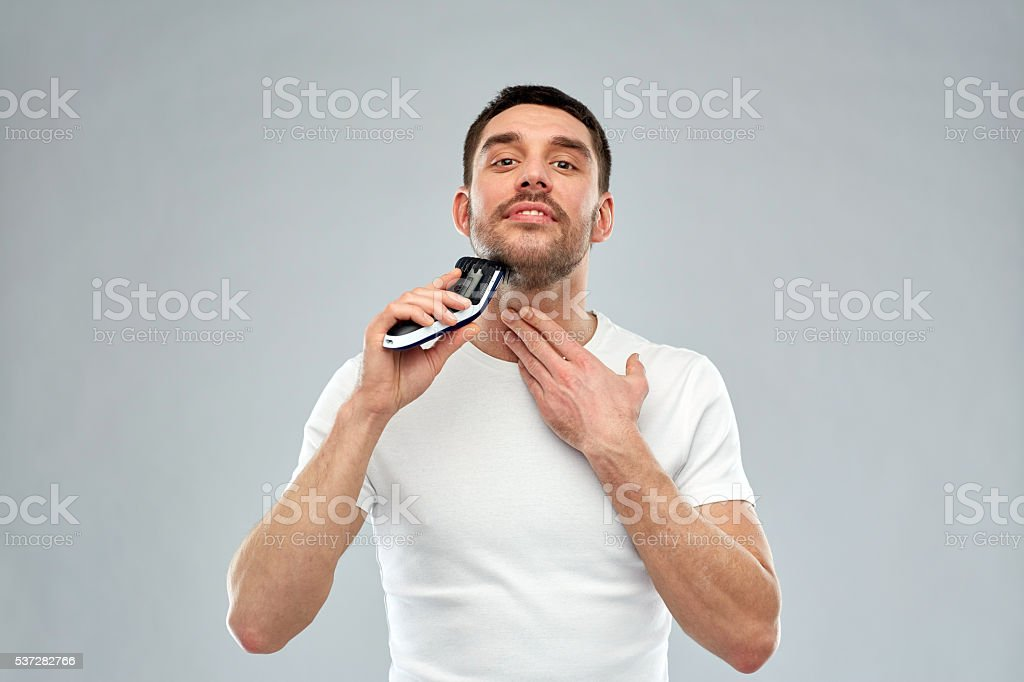 smiling man shaving beard with trimmer over gray stock photo
