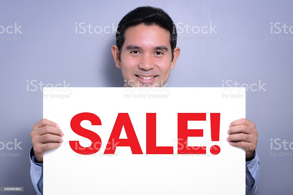 Smiling man showing SALE! sign stock photo