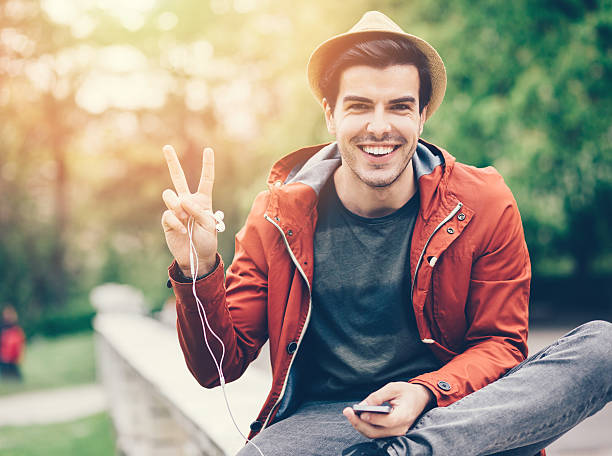 smiling man showing the peace sign - symbols of peace stock pictures, royalty-free photos & images
