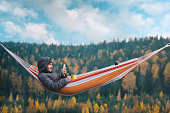 istock A smiling man sits in a hammock and uses a smartphone in a picturesque location. Mug in his right hand. 1065016406