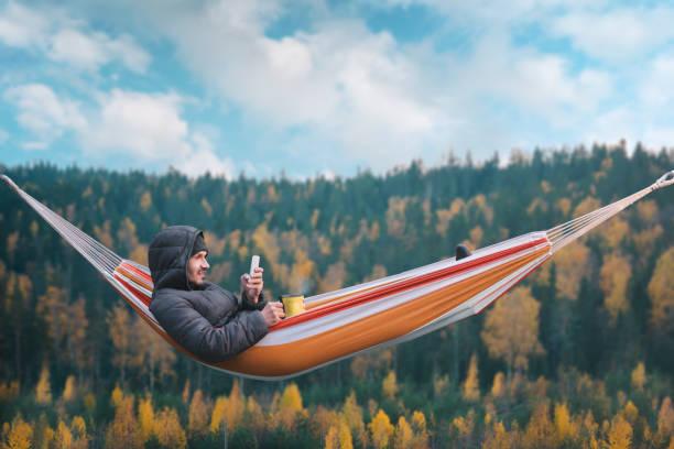 en leende man sitter i en hängmatta och använder en smartphone i ett pittoreskt läge. mugg i högra handen. - norrbotten bildbanksfoton och bilder