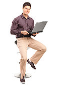 istock Smiling man sitting and working on a laptop 471855953
