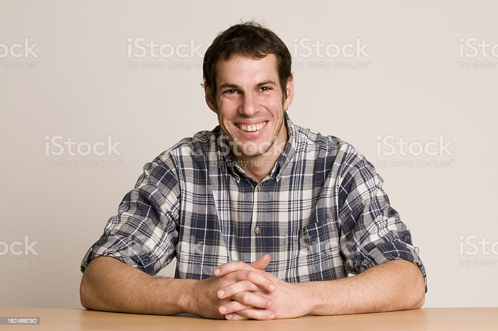 smiling man sitting at table stock photo