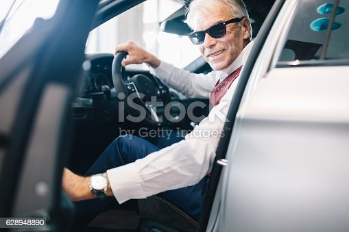 1138561232 istock photo Smiling man sitting at the driver's seat 628948890