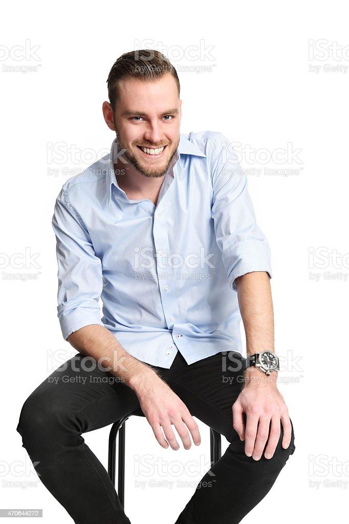 Smiling man sitting down stock photo