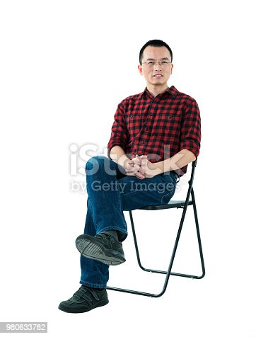 istock Smiling man sitting on chair 980633782