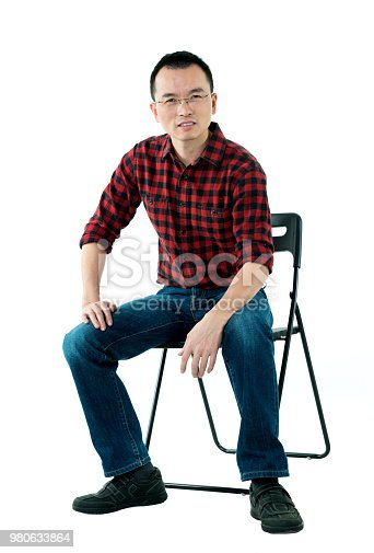 istock Smiling man sitting on chair 980633864