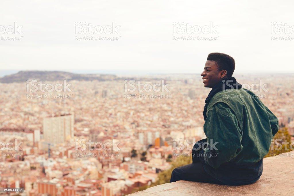 Homem sentado no terraço com vista para a cidade a sorrir - foto de acervo