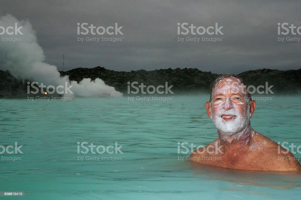 Smiling man soaking in hot springs stock photo