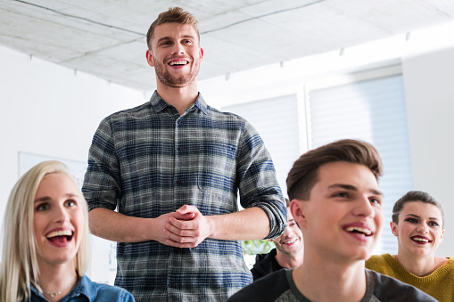 Smiling Man Standing By Friends During Meeting Stock Photo - Download Image Now