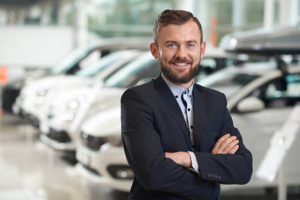 Smiling man standing in modern car center and posing. Front view of handsome man standing in modern car center and posing. Bearded manager wearing in dark blue jacket smiling and looking at camera. Row of automobiles on background. car salesperson stock pictures, royalty-free photos & images