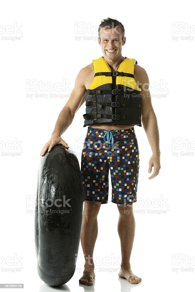 Smiling man standing with an inner tube stock photo
