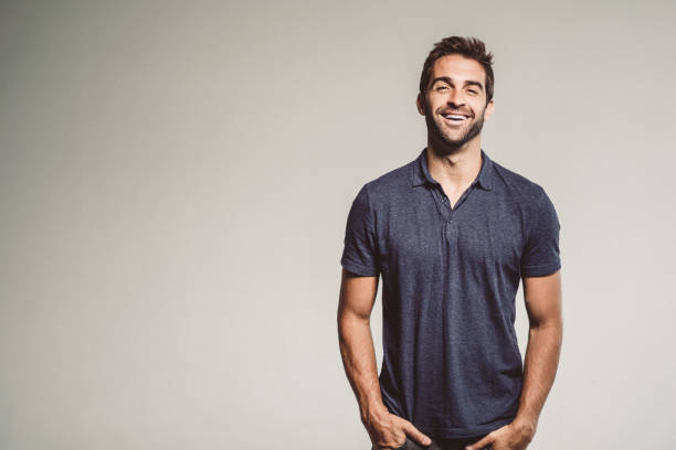 Smiling man standing with hands in pockets stock photo
