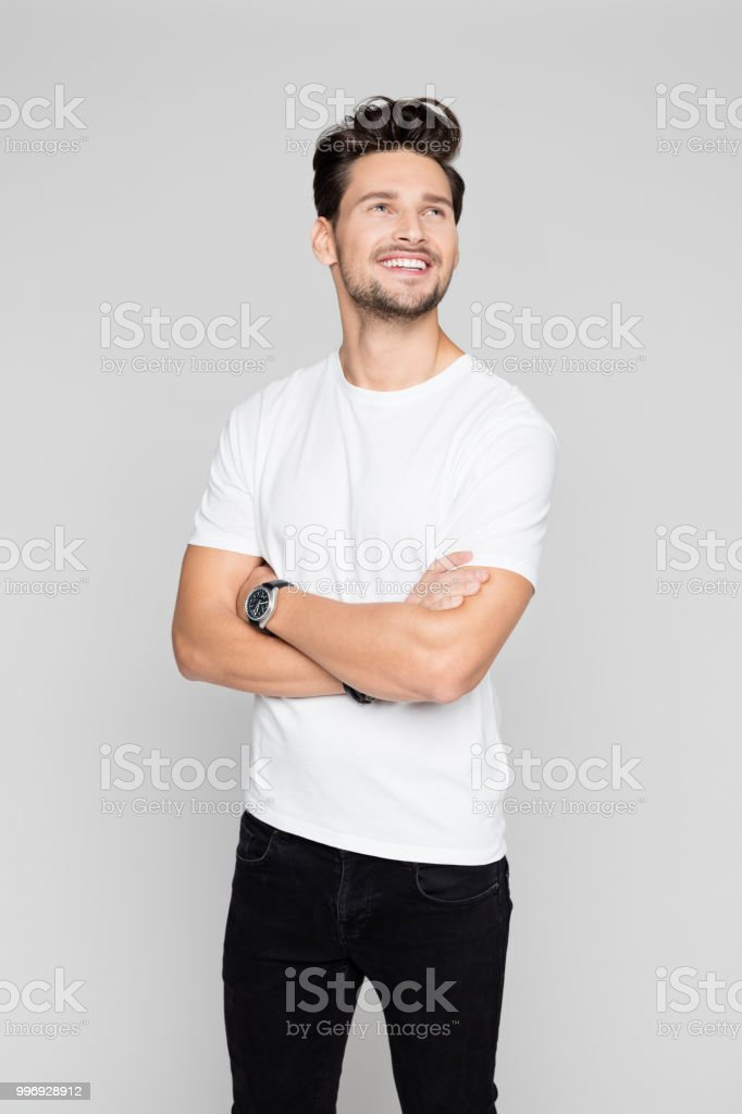 Smiling man standing with his arms crossed Portrait of smiling man standing with his arms crossed and looking away on grey background 25-29 Years Stock Photo