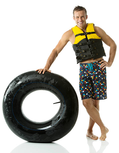 Smiling man standing with inner tube stock photo