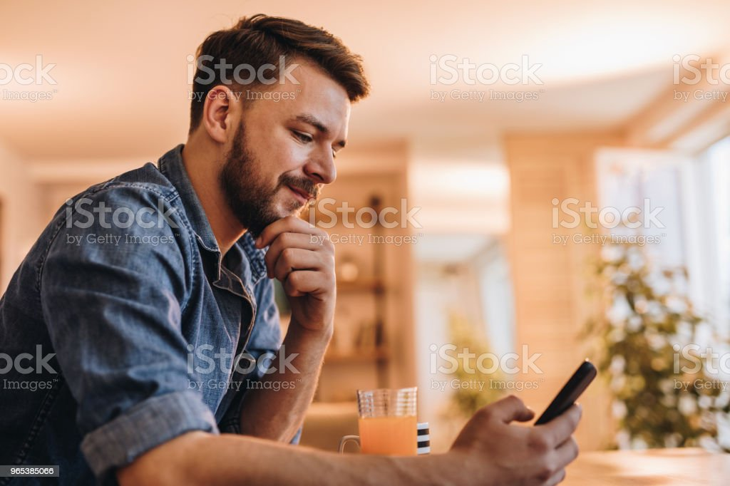 Smiling man surfing the Internet on his mobile phone at home. royalty-free stock photo