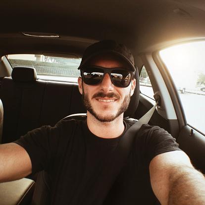 Smiling man take a selfie on his car