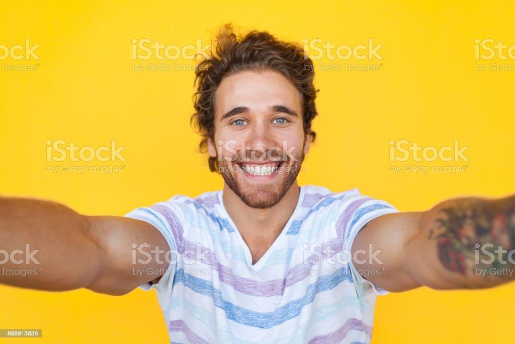 Smiling man taking selfie stock photo