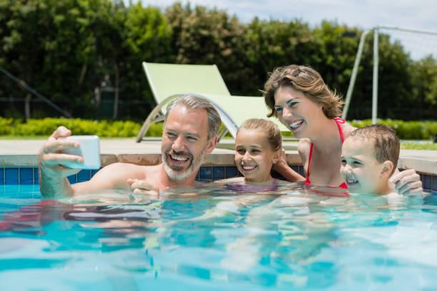 lächelnder mann unter selfie mit familie im schwimmbad - senior bilder wasser stock-fotos und bilder