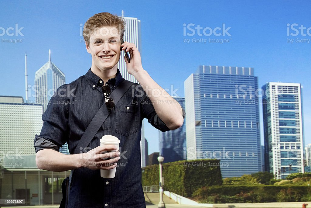 Smiling man talking on mobile phone in front of city royalty-free stock photo