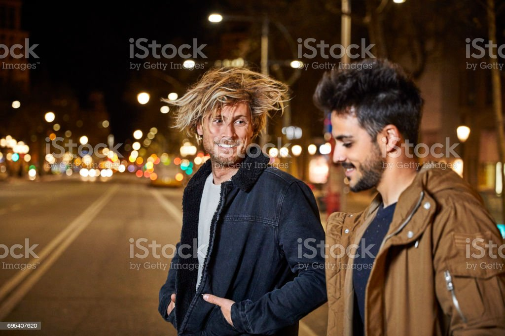 Smiling man talking to friend on street at night stock photo