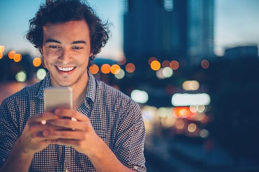 Smiling man texting at night