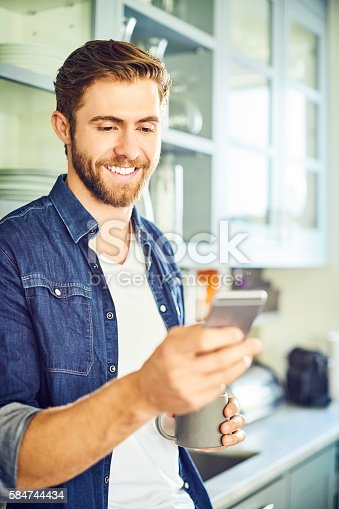 Smiling man texting through smart phone while holding coffee cup. He is in casuals. Happy male is in kitchen.
