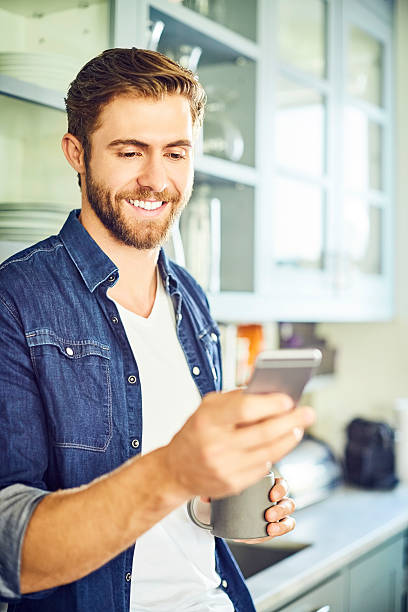 Smiling man texting through smart phone while holding coffee cup – Foto