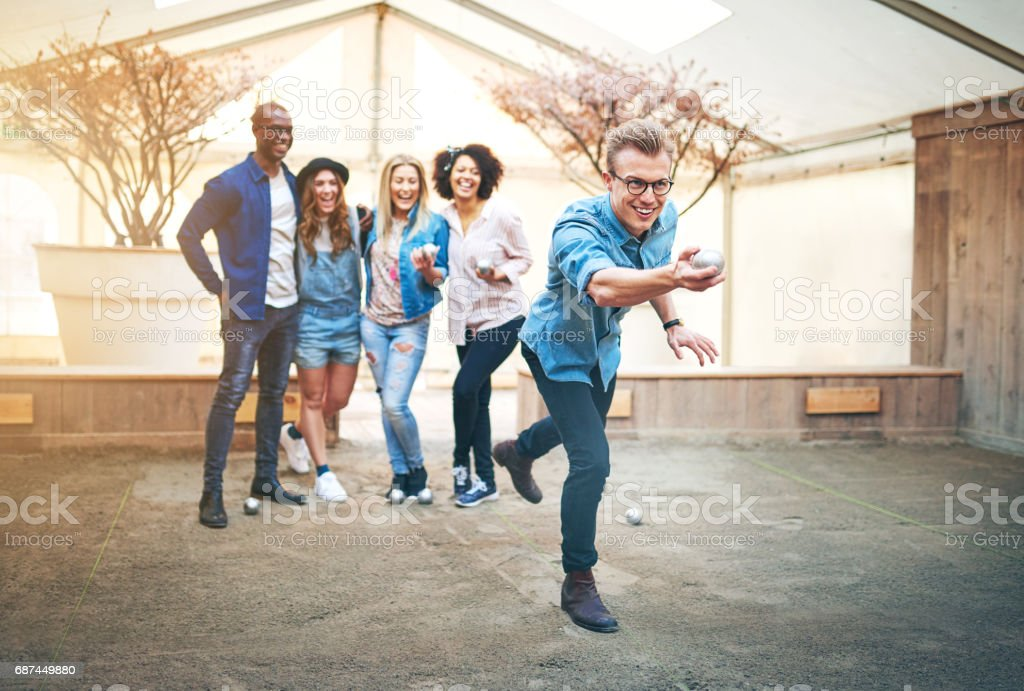 Smiling man throwing ball for petanque while team cheering him stock photo