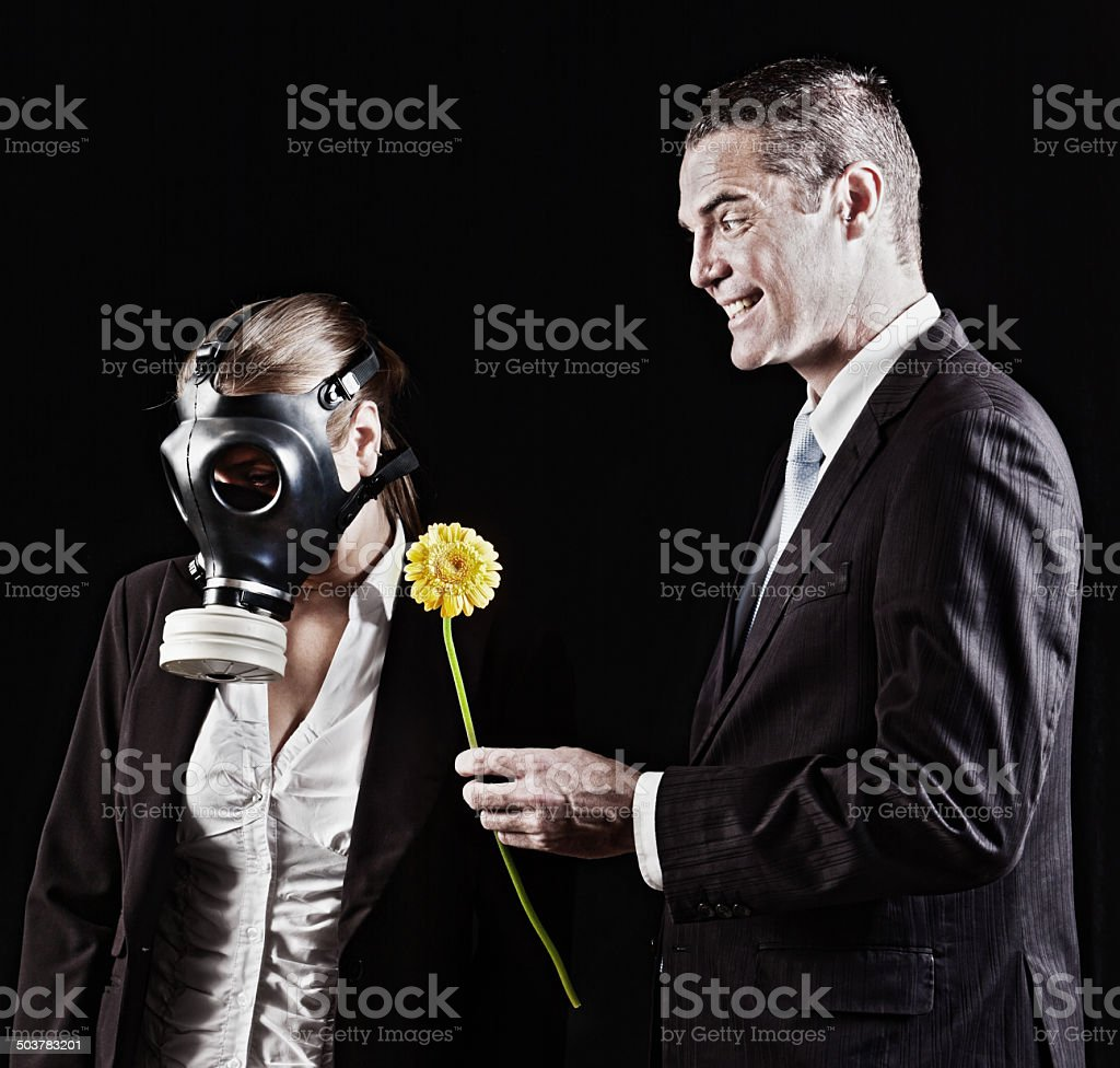 Smiling man tries his luck with woman in gasmask stock photo