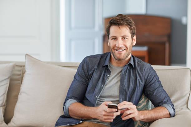 Lächelnder Mann mit einem Handy auf seinem Sofa zu Hause – Foto