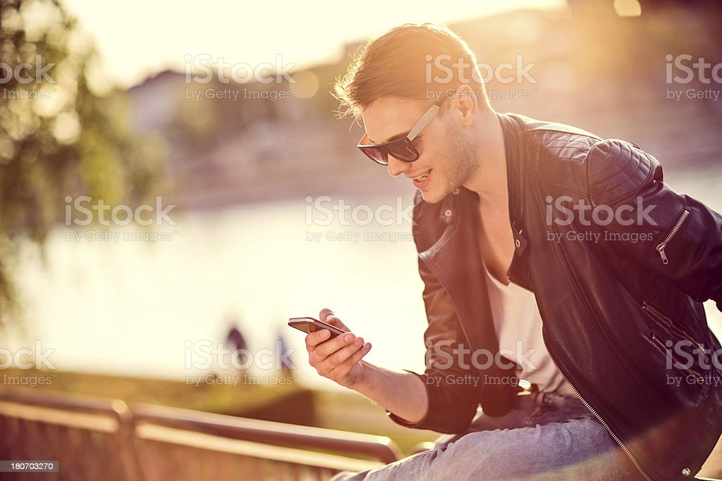 Smiling man using a smart phone outdoors royalty-free stock photo