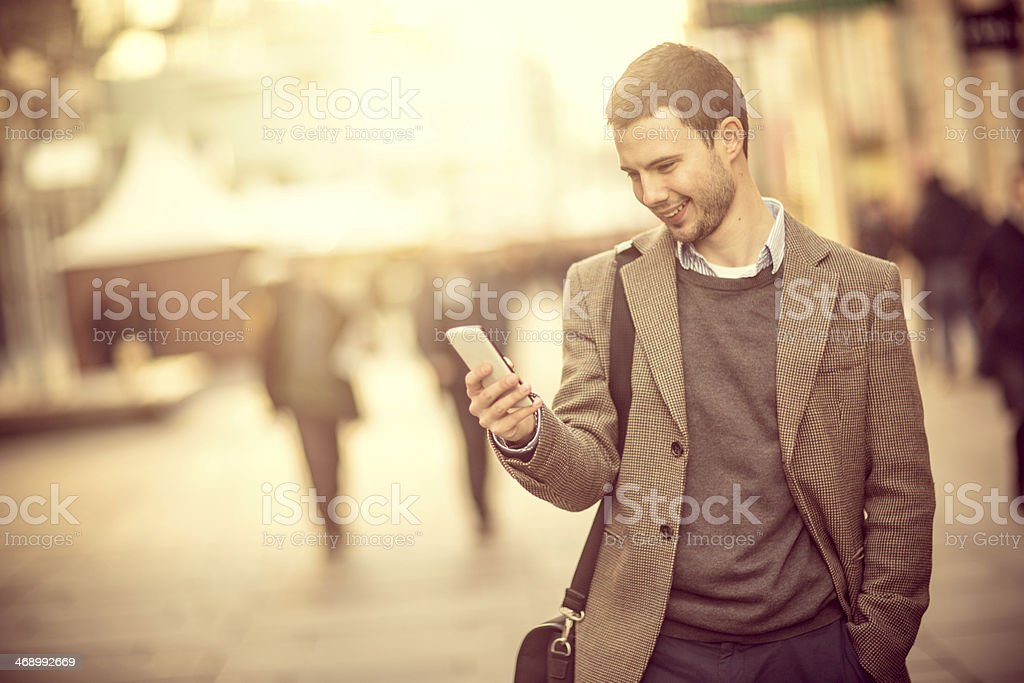 Smiling man using a smartphone on the street stock photo