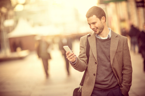 Smiling Man Using A Smartphone On The Street Stock Photo - Download Image Now