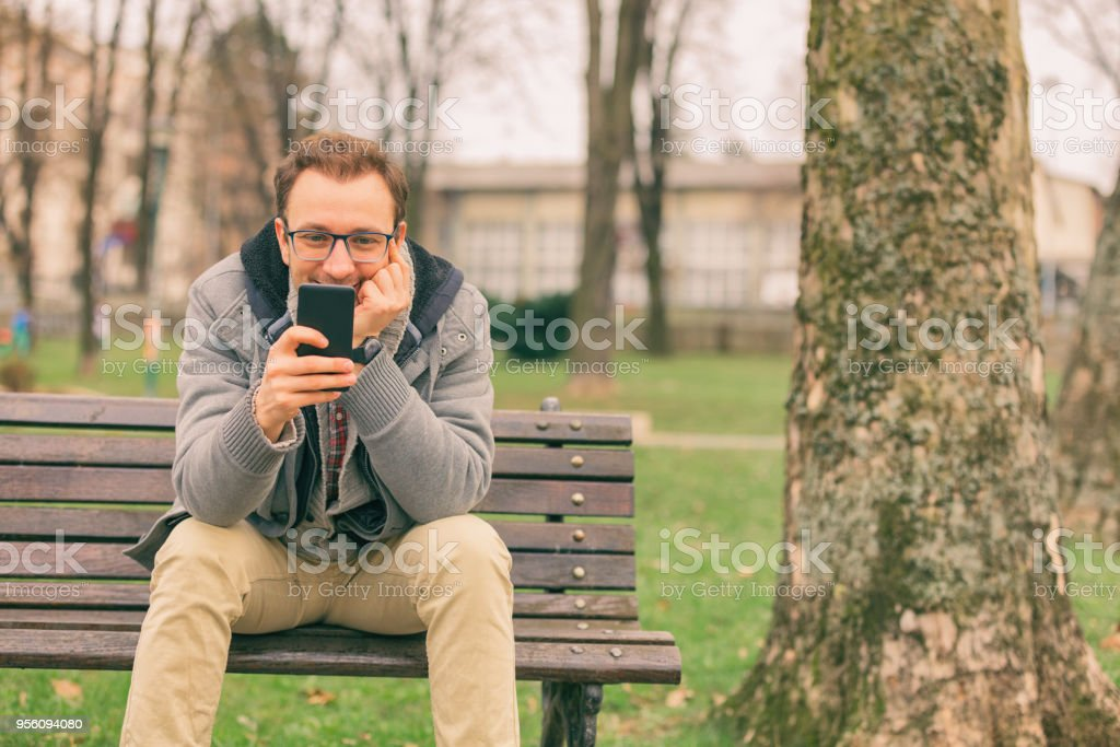 Smiling man using cellphone while sitting on the bench. stock photo