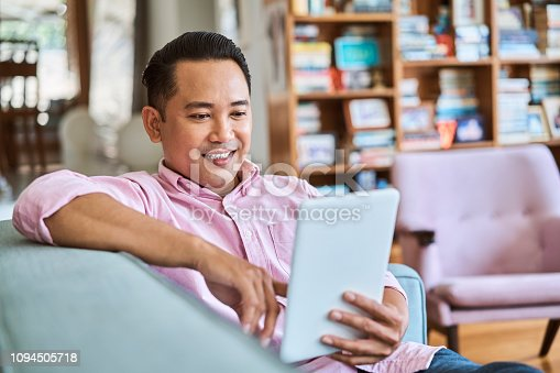 Smiling man using digital tablet in living room. Confident handsome male is sitting on sofa. He is in pink shirt at home.