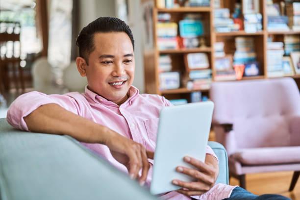 Lächelnder Mann mit digital-Tablette im Wohnzimmer – Foto