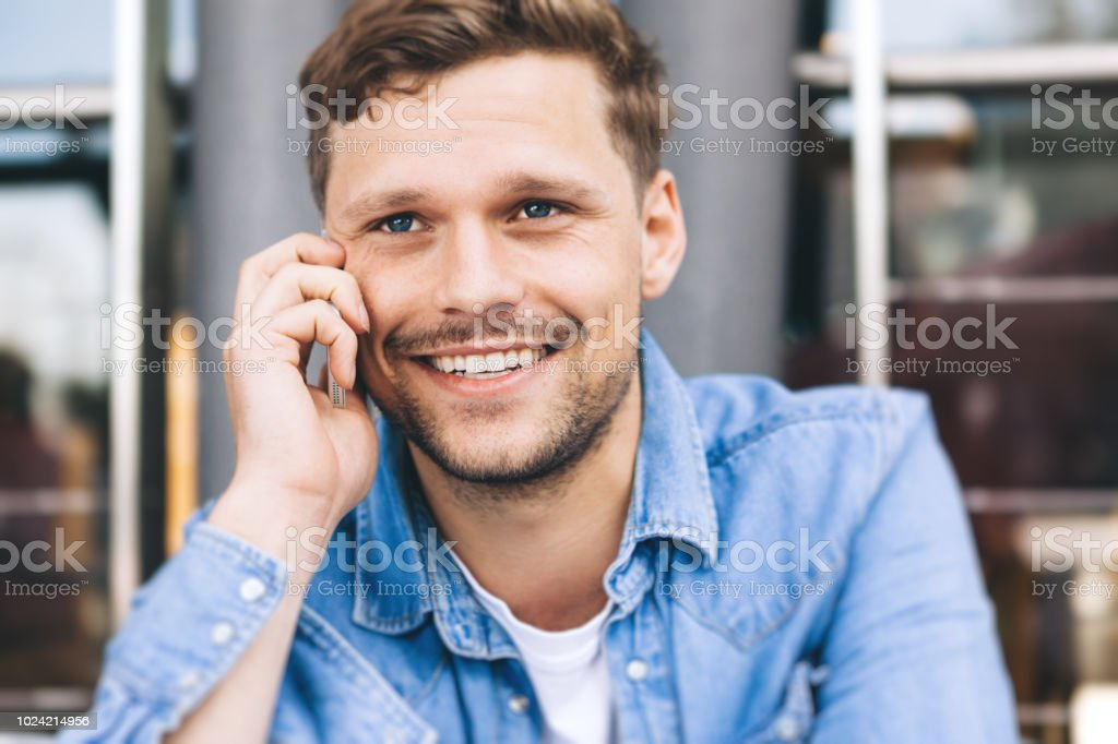 smiling man using his cellphone stock photo