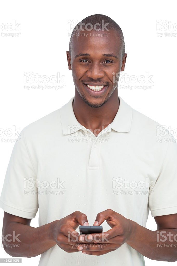 Smiling man using his mobile phone stock photo