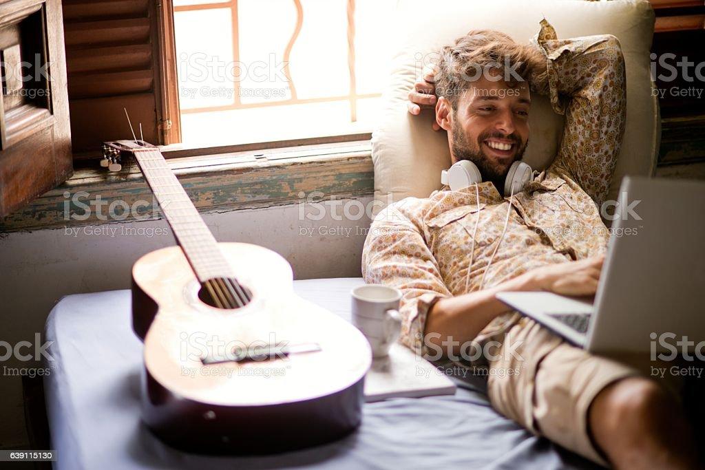 Smiling man using laptop stock photo