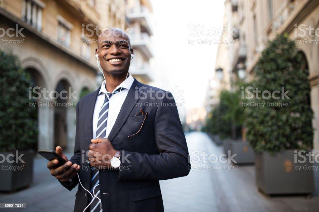 Smiling man using mobile phone. stock photo