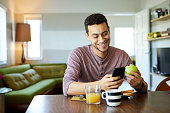 istock Smiling man using mobile phone while holding apple 1133527295
