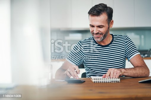 Smiling man using notebook and calculator to manage home budget